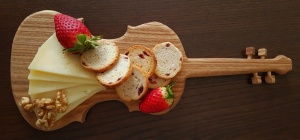 Cheese, strawberry, nuts and crusty bread on wooden cutting board in the form of violin. Top view